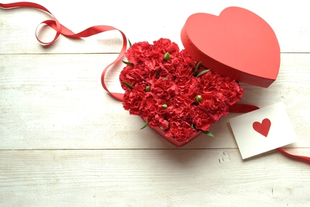shaped: Heart shaped red carnations box with message card Stock Photo