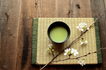 maccha: A cup of green tea with cherry blossoms on the tatami mat