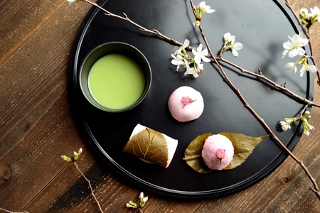 Cherry flavored Japanese sweets and green tea on the black tray