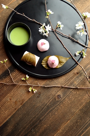 maccha: Cherry flavored Japanese sweets and green tea on the black tray