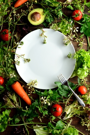 White dish on the fresh vegetables with rocket flowers Stock Photo