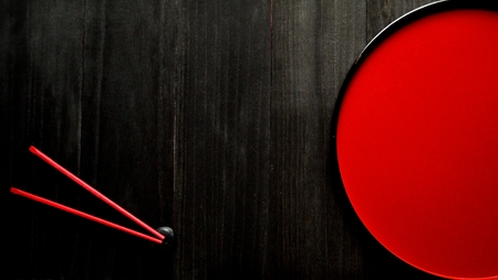 lacquer ware: Japanese red tray and red chopsticks on black wooden background