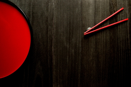 Japanese red tray and red chopsticks on black wooden background Фото со стока - 61882135