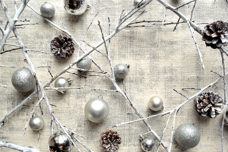 Silver Christmas ornament balls, dead branch and pine cones