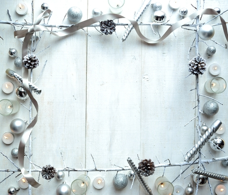 Silver Christmas ornaments with ribbon.frame.white wooden background