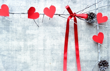 Red heart shaped paper cut out with red ribbon