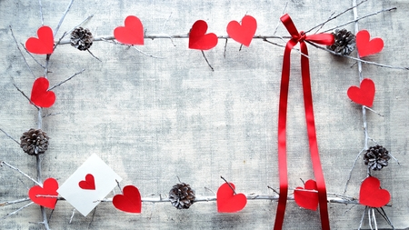 Red heart shaped paper cut out, red ribbon and the message card
