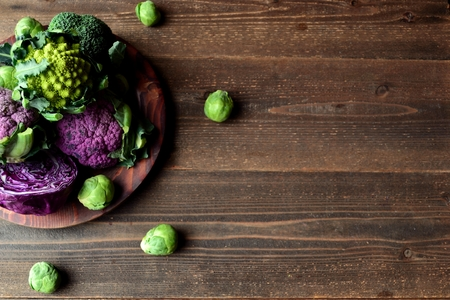 green and purple: Purple cauliflower and broccoli served on a wooden dish