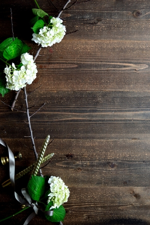 White hydrangeas with candle sticks on the black wooden background