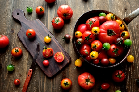 Colorful tomatoes on the saucepan with cutting boad
