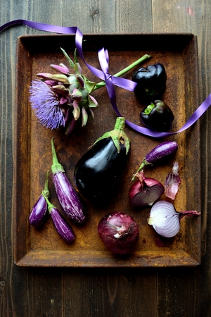 Artichoke and eggplants on the rusted tray