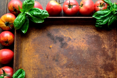 Tomatoes, basil leaves and rusted tray Stock Photo