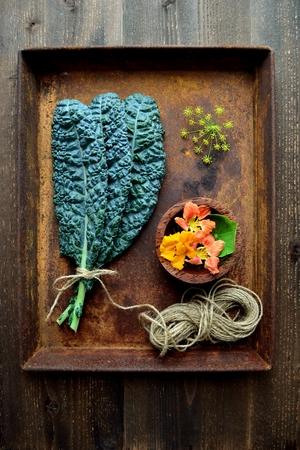 Kale bladeren met nasturtium bloemen op de roestbak