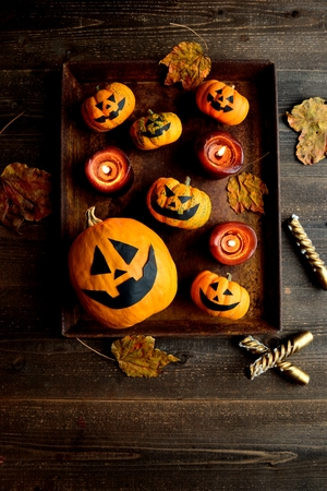 Halloween pumpkins with candles on the rusted tray