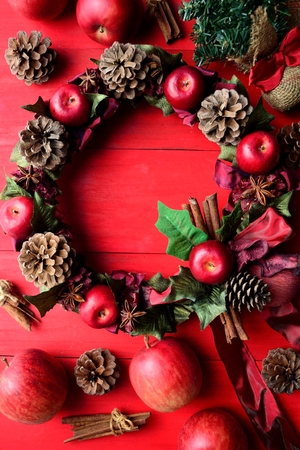 Red apples Christmas wreath on the red background Stock fotó