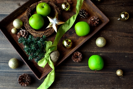 Christmas tree with green apples on the rusted tray