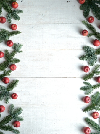 Fir leaves and apples on the white wooden background Foto de archivo