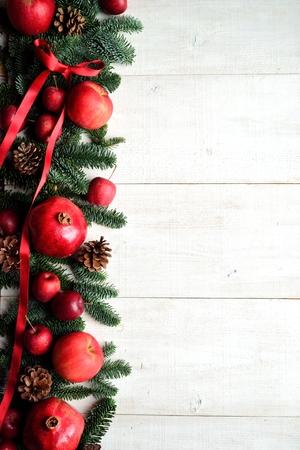 Pomegranate, apples and fir leaves.frame