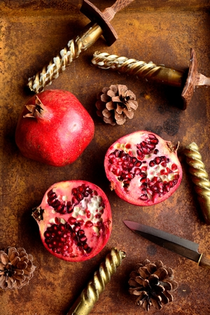 Pomegranates with candles on the rusted tray