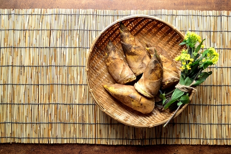 Bamboo shoots with rape blossoms on the basket. Japanese style blind background