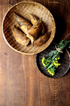 Bamboo shoots with rape blossoms on the baskets Imagens