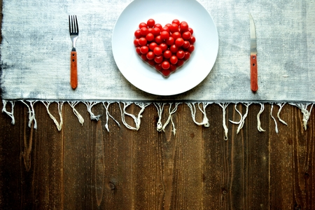 Cherry tomatoes on a white dish.heart shaped 写真素材 - 107381529