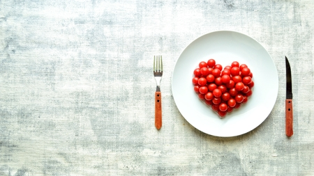 Cherry tomatoes on a white dish.heart shaped 写真素材 - 107381808