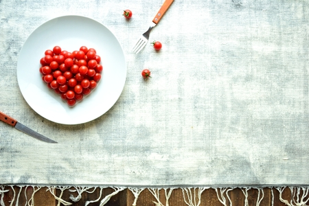 Cherry tomatoes on a white dish.heart shaped