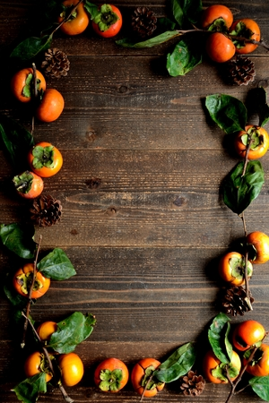 Persimmons on the black wooden background 스톡 콘텐츠