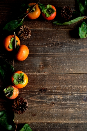 Persimmons on the black wooden background Reklamní fotografie