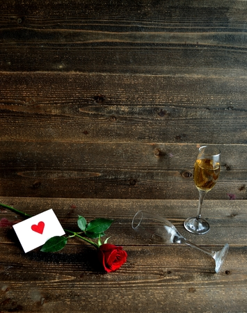A single red rose, the message card and champagne glasses Stock Photo