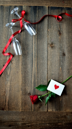 A single red rose, the message card and champagne glasses Imagens