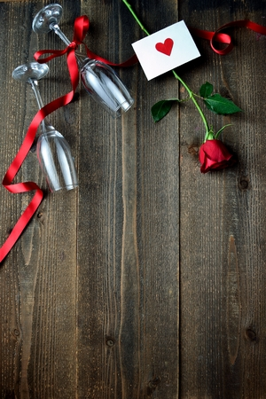 A single red rose, the message card and champagne glasses Фото со стока