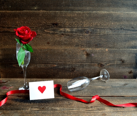 A single red rose, champagne glass and the message card
