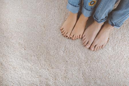 Dos pares de pies en jeans descansando sobre una alfombra suave