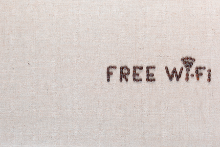 Free wifi sign made from coffee beans on linea background, shot top view, aligned middle right. Foto de archivo - 122486385
