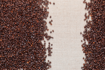 Roasted coffee beans arranged on sides of linea canvas leaving an open space on the right, shot from above. Foto de archivo - 122490752