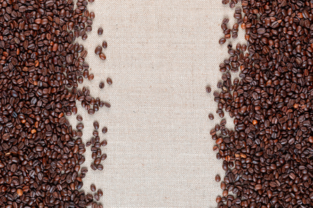 Roasted coffee beans arranged on sides of linea canvas leaving an open space in middle, shot close up from above. Foto de archivo - 122490753