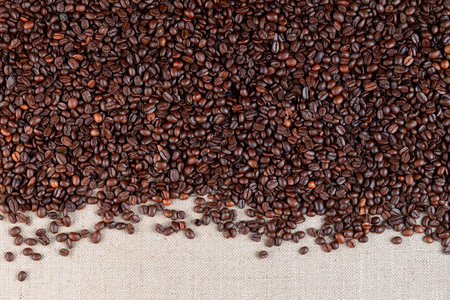 Roasted coffee beans arranged on top of linea canvas leaving a narrow open space on the bottom, shot from above. Foto de archivo - 122500371