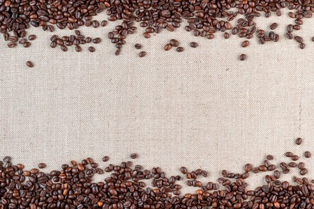 Roasted coffee beans arranged on top and bottom sides of linea canvas leaving an open space in middle, shot from above. Foto de archivo - 122500377
