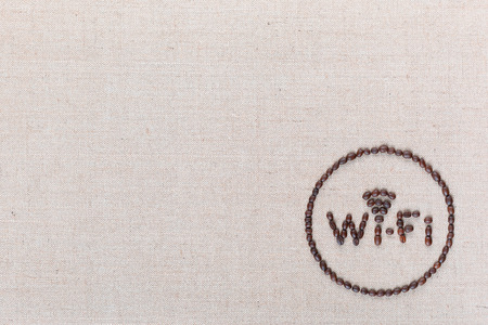 WiFi sign made from roasted coffee beans enclosed in circle isolated on creamy linea background shot top view, aligned bottom right.