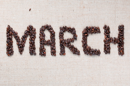 Month march written with roasted coffee beans on creamy linea canvas aligned in the center. Foto de archivo - 122487930