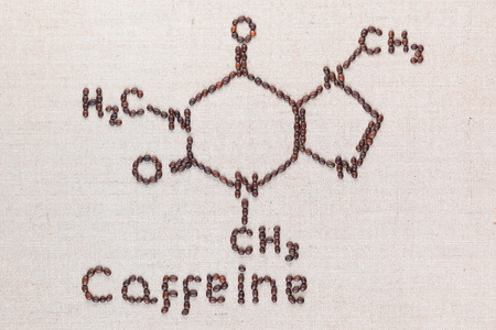 Caffeine written with letters under chemical formula made from roasted coffee beans on creamy linea canvas, shot top view, aligned in center.