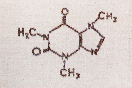 Caffeine chemical formula made from roasted coffee beans on creamy linea canvas, shot top view, aligned in center. Foto de archivo - 122278503