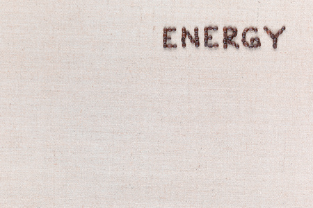 Energy word made with capital letters from roasted coffee beans on creamy linen canvas, shot from above, aligned top right.