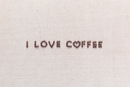 'I love coffee' words made from roasted coffee beans on linen texture, shot from above, aligned centered.