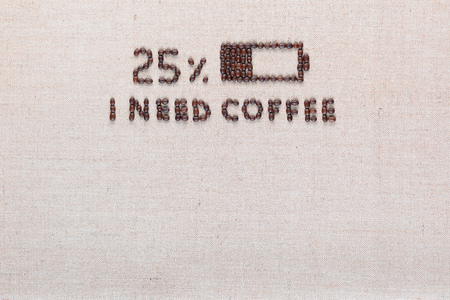 Low level battery with 'I need coffee' sign made from roasted coffee beans on creamy linen canvas, shot from above, aligned top center.