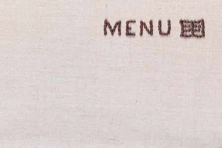 Menu word with icon made from roasted coffee beans on linen creamy linen canvas, shot from above, aligned top right. 스톡 콘텐츠