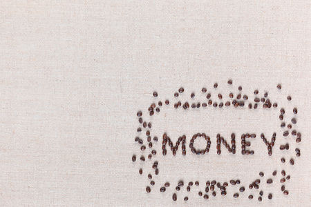 Money word surrounded by roasted coffee beans on creamy linen canvas, shot from above, aligned bottom right.
