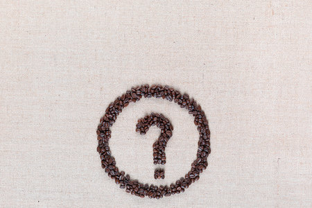 Question mark enclosed in circle made from coffee beans on creamy linen fabric, shot from above, aligned bottom center. Banco de Imagens